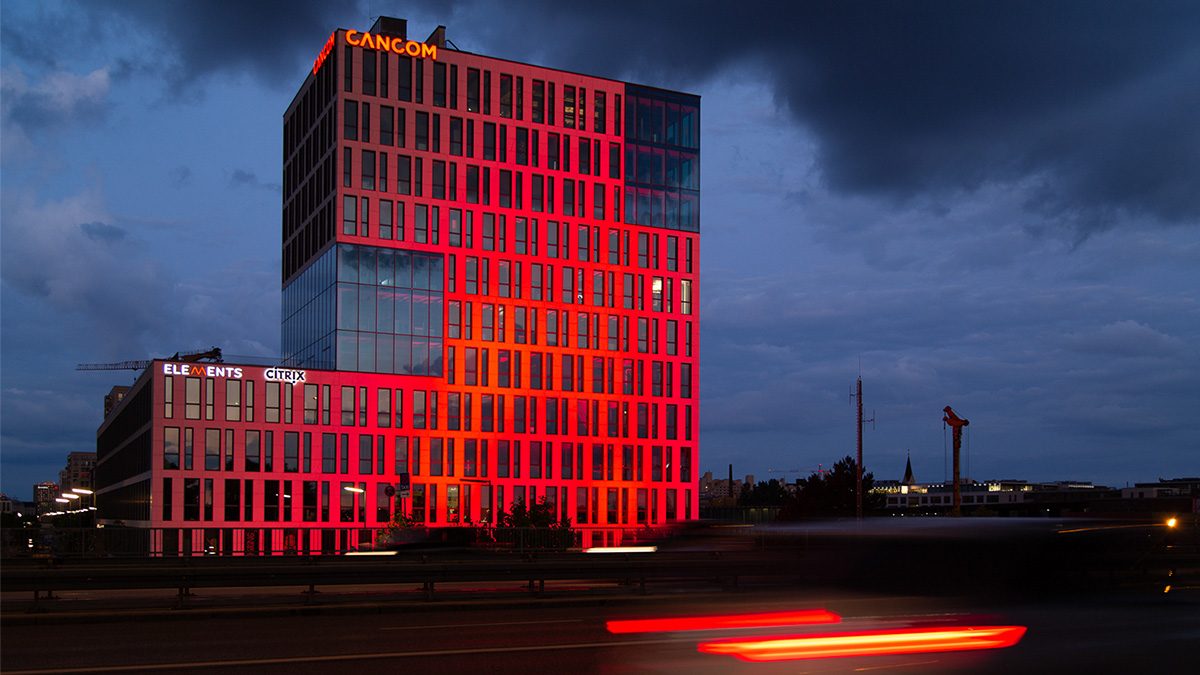 CANCOM Bürogebäude bei Nacht mit erleuchtendem rotem Schriftzug