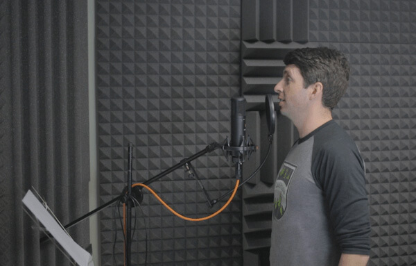 Person speaking into a microphone in an audio recording room