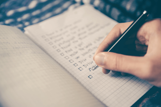 pen in hand writing a checklist